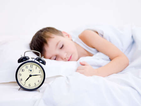 Little boy sleeping with alarm clock near his head photo