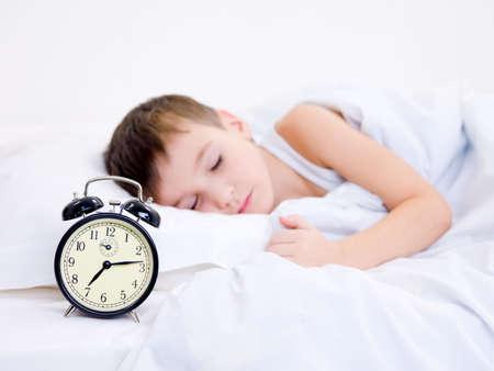 Little boy sleeping with alarm clock near his head photo