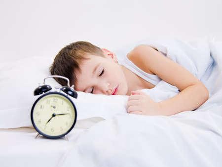 enfant qui dort: Kid doux veille avec le r�veil pr�s de sa t�te.  Banque d'images