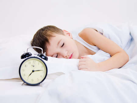 early: Sweet kid sleeping with alarm clock near his head Stock Photo