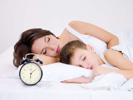Young mother and son sleeping on a bed. �larm clock on foreground  photo