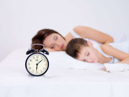 Beautiful young mother and her preschool son sleeping with alarm clock  photo