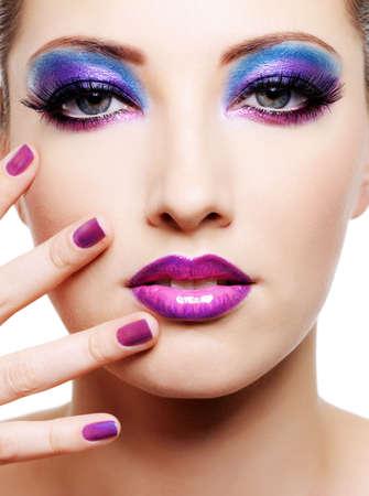 Bella faccia femmina giovane con brillante moda trucco multicolore e bellezza viola manicure delle unghie