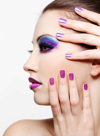 Woman with Beautiful  face and  fashion style make-up and beauty purple manicure of fingernails photo