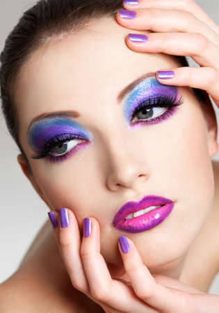 Beautiful  female face with fashion  make-up of eyes and beauty purple manicure. She put her hands on face. Stock Photo - 6101726