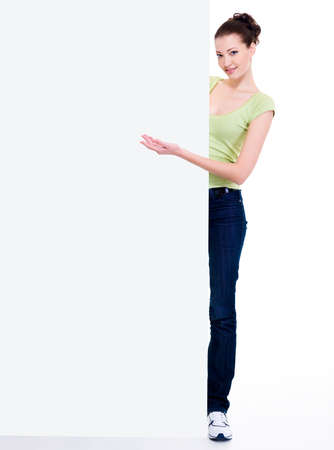 Beautiful smiling woman points  on the blank billboard by hand Stock Photo - 6101748