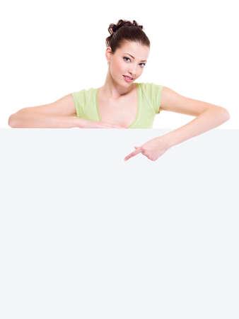 집게 손가락: Beautiful sexy cuacasian woman under the white blank banner points by forefinger on it  스톡 사진