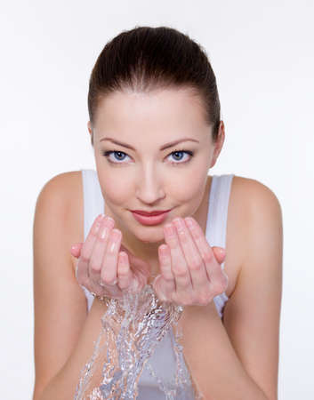 beautiful young woman washing her face with water  photo