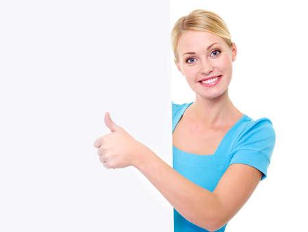 dentudo: Feliz hermosa mujer sonriente toothy mira desde de la titularess y demostrando pulgares telef�nico Foto de archivo