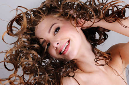 ringlet: Low angle portrait of the cheerful smiling woman with long curly hairs