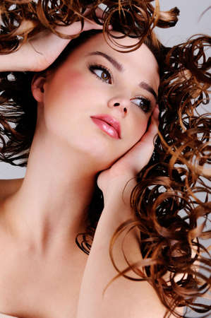 Closeup face of the beautiful girl with  long curly hairs - low angle photo