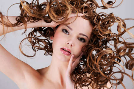 Low angle portrait of the beautiful  woman with  long curly hairs photo