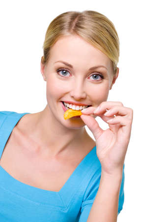 Portrait of a happy beautiful woman eats the chips - over white background. Copy space photo