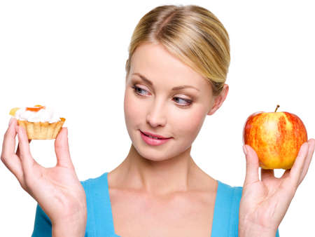 healthy choices: Young beautiful female choose  from sweet cake and red apple