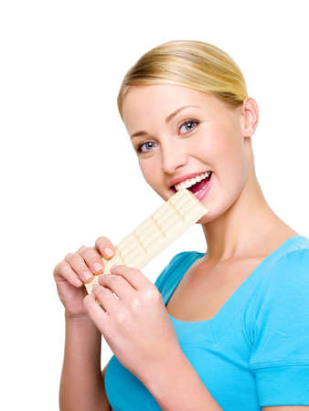 bl: Beautiful happy woman eats the sweet white  porous chocolate - isolated on white   Stock Photo