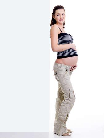 mujeres embarazadas: Feliz y atractiva mujer embarazada de pie cerca de banner en blanco blanco Foto de archivo