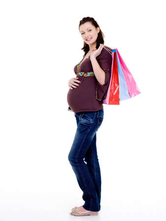 Full-length photo of a Beautiful cheerful pregnant woman with shopping bags photo