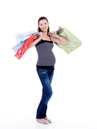 Beautiful happy smiling pregnant woman with shopping bags - isolated on white photo