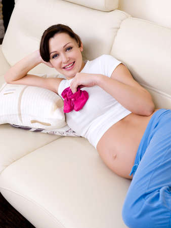 baby's bootee: Young smiling Pregnant woman  with babys bootee  Stock Photo