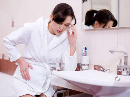 The pregnant woman with a strong toxicosis sitting in bathroom Stock Photo - 6220910