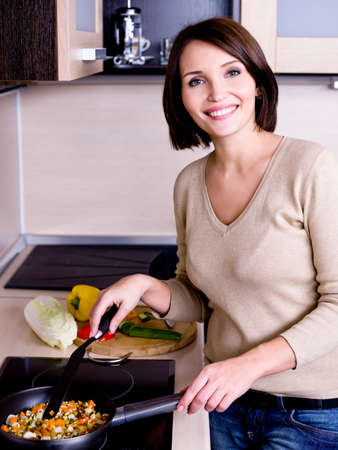 The joyful beautiful woman is on the kitchen prepares to eat  photo