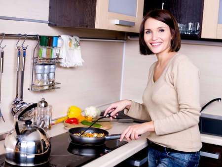 cooker: The joyful beautiful woman is on the kitchen prepares to eat  Stock Photo