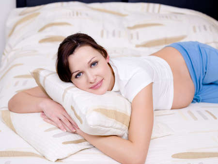 8 9 months: Beautiful brunette pregnant woman lying on the sofa