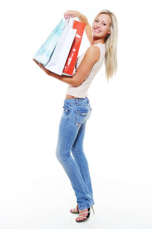 Happy beautiful woman with bags after shopping - full-length portrait photo