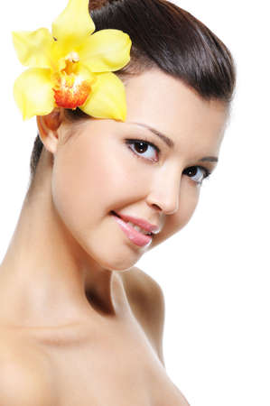 Face of a beauty happy young asian woman with yellow orchid from her ear - over white background photo