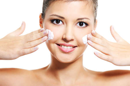 Beauty asian smiling young adult girl apply cosmetic cream on her face photo