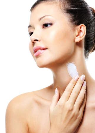 Beautiful asian female  applying cosmetic moisturizer  cream on neck photo