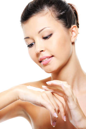 Beautiful pretty young girl caring of her hands treatment cosmetic cream photo
