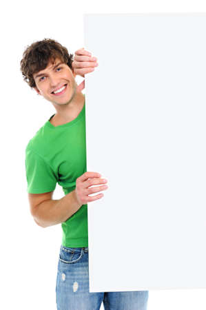 Happy cheerful guy look out from blank billboard - over white background photo