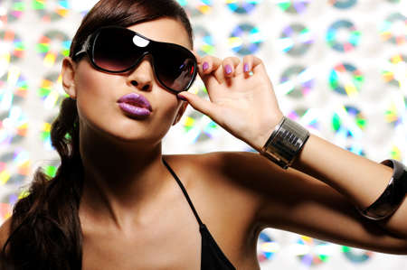 Beautiful  woman in the black fashion sunglasses touching it - pouting sexy lips photo
