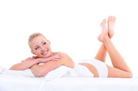 Happy cute beautiful smiling woman lying on the soft bed photo