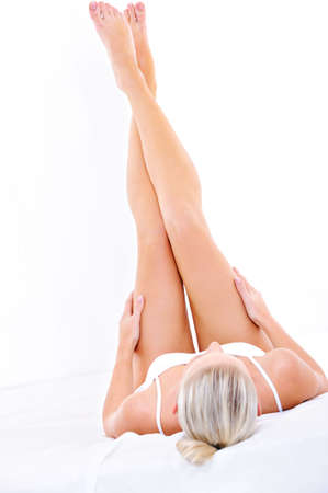young woman legs up: Young woman lying down on the bed and stroking her perfect legs