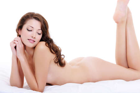 young naked girl: Sexy nude body of a pretty young female lying down on the bed Stock Photo