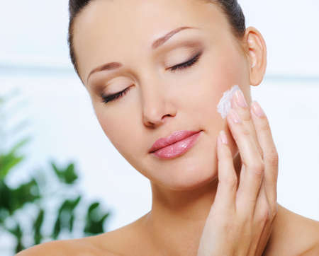Candid woman face with closed eyes applying  moisturizer cream on her cheek photo