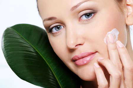 Woman applying moisturizer  cream on her  fresh beauty face with a leaf at face photo