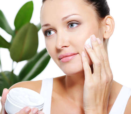 woman face cream: Beautiful adult woman applying moisturizer cream for her pretty face