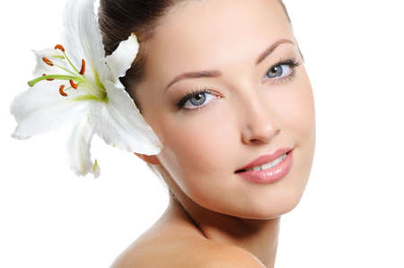 unblemished: Pretty beautiful woman face with health skin and white lily in her hairs