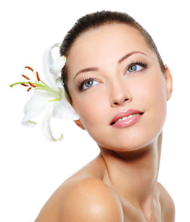 feminity: Skincare of young beautiful woman face with  fresh flower over white background