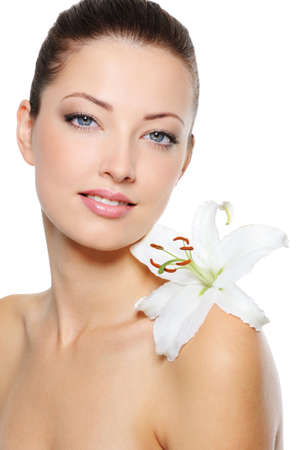 Beautiful clear female face with health skin and white lily on her shoulder Stock Photo - 6511741