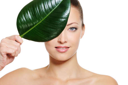 Perfect caucasian woman face covering with a fresh green leaf photo