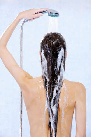 douche: Young female with douche standing back with stream water on head  Stock Photo