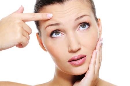 jonge aantrekkelijke vrouw toont door wijsvinger de rimpels op haar voorhoofd