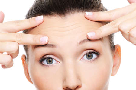 cosmetology: Female face with wrinkles on forehead - skincare treatment