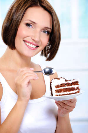 The beautiful smiling young woman with a cake slice on a plate photo