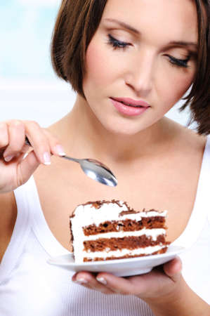 The beautiful young woman overcome by a temptation to eat a slice of a sweet cake  photo