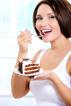 The beautiful cheerful young woman eats a sweet cake   photo